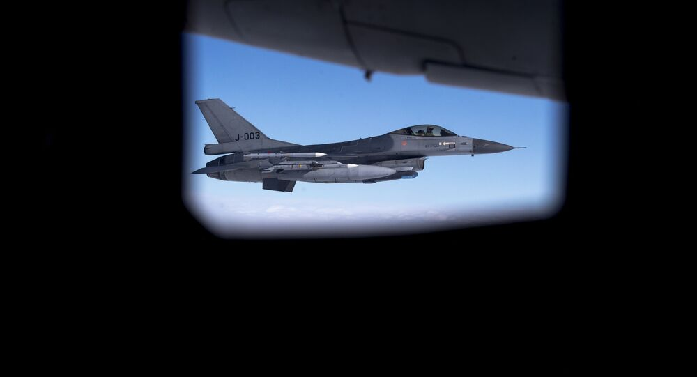 Seen through the window of another aircraft, an Royal Netherlands Air Force F- 16 military fighter jet participating in NATO's Baltic Air Policing Mission operates in Lithuanian airspace during a Ramstein Alloy air force exercise, Tuesday, April 25, 2017