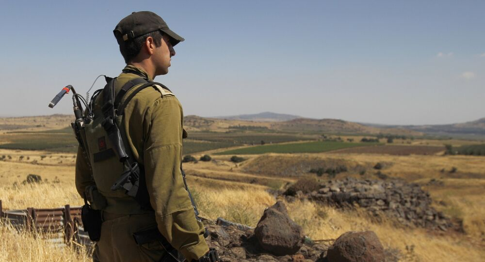 A Israeli soldier patrols near the border with Syria after projectiles fired from the war-torn country hit the Israeli occupied Golan Heights on June 24, 2017