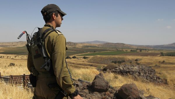 A Israeli soldier patrols near the border with Syria after projectiles fired from the war-torn country hit the Israeli occupied Golan Heights on June 24, 2017 - Sputnik International