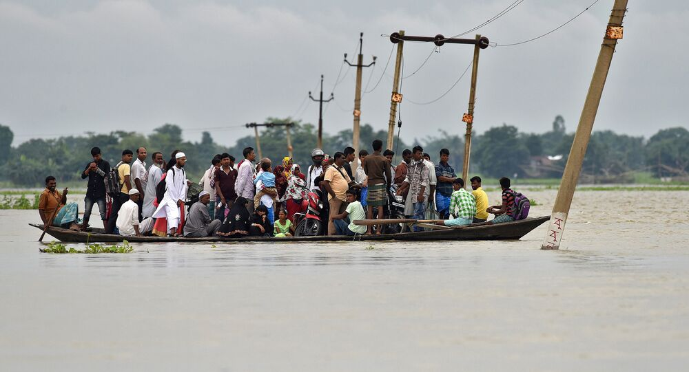 Villagers use a boat to cross a flooded road at Asigarh village in Morigaon district in the northeastern state of Assam, India, July 4, 2017