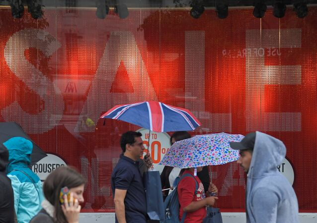 Shoppers walk past a sale sign in central London, Britain June 27, 2017.