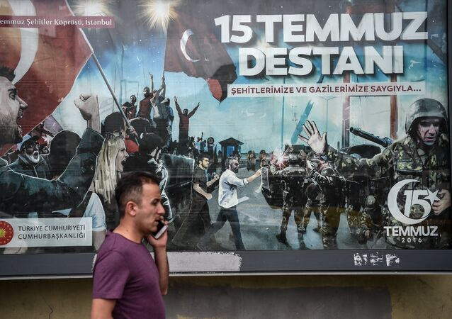 A man at phone walks past a giant billboard reading Legend of July 15 for the anniversary of the last year's attempted coup in Turkey, on July 14, 2017 in Istanbul