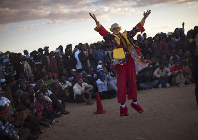 A clown performs to entertain people near to a refugee camp (File)