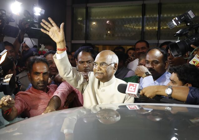 Ram Nath Kovind, center, waves to media upon arrival at the airport in New Delhi, India, June 19, 2017