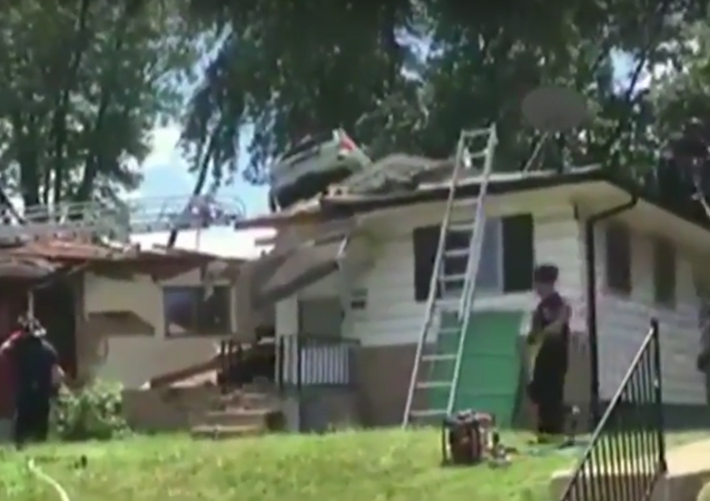 an SUV lands on top of a home in St. Louis, Missouri.