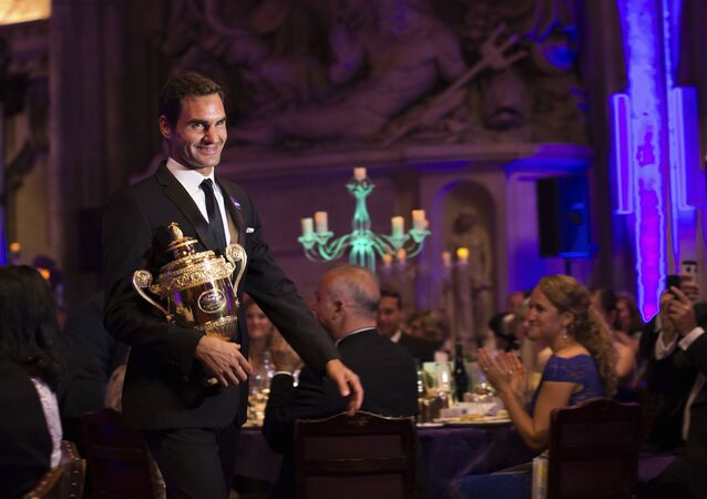 The 2017 Wimbledon Men's Singles champion Roger Federer of Switzerland arrives with his trophy for the Champions Dinner at The Guildhall in London, late Sunday July 16, 2017.