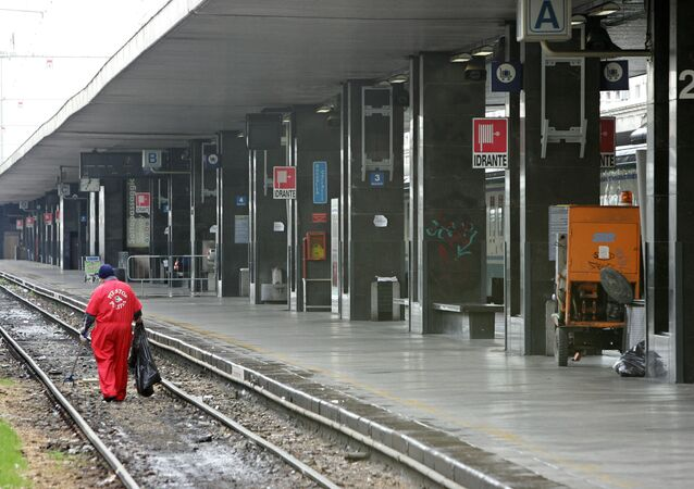 A worker cleans a railway track near an empty platform of the Termini station in Rome.