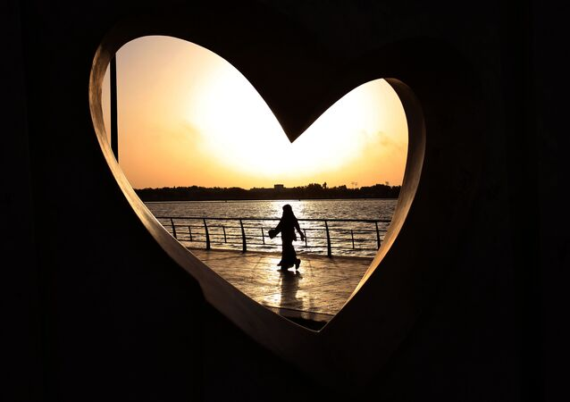 Saudi woman seen through a heart-shaped statue walks along an inlet of the Red Sea in Jiddah, Saudi Arabia