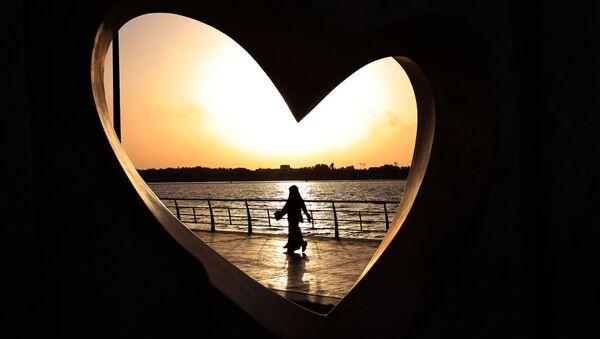 Saudi woman seen through a heart-shaped statue walks along an inlet of the Red Sea in Jiddah, Saudi Arabia - Sputnik International