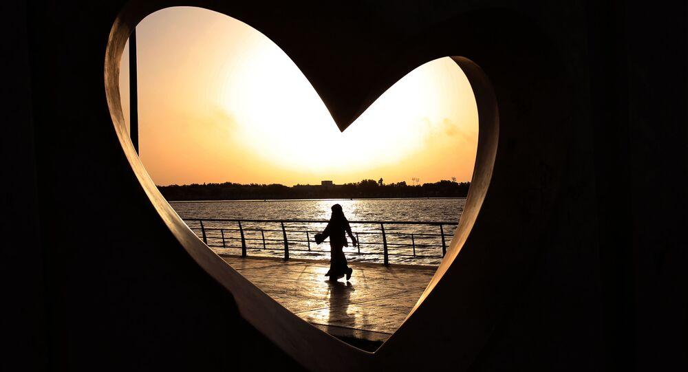 Saudi woman seen through a heart-shaped statue walks along an inlet of the Red Sea in Jiddah, Saudi Arabia