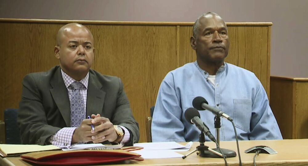 Former NFL football star O.J. Simpson appears with his attorney, Malcolm LaVergne, left, via video for his parole hearing at the Lovelock Correctional Center in Lovelock, Nev., on Thursday, July 20, 2017.