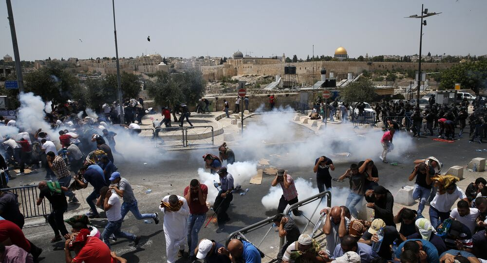 Palestinian worshippers run for cover from teargas, fired by Israeli forces, after prayers outside Jerusalem's Old City in front of the Al-Aqsa mosque compound after Israeli police barred men under 50 from entering the Old City for Friday Muslim prayers as tensions rose and protests erupted over new security measures at the highly sensitive holy site on 21 July 2017.