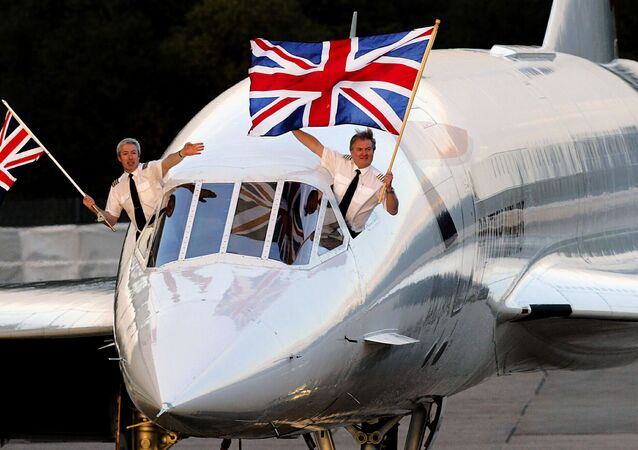 Concorde captain Mike Bannister (R) with the Union Jack flag and senior first officer Jonathan Napier (L) wave as they complete the last supersonic Concorde flight from New York, BA 002, at Heathrow international airport in London 24 October 2003.