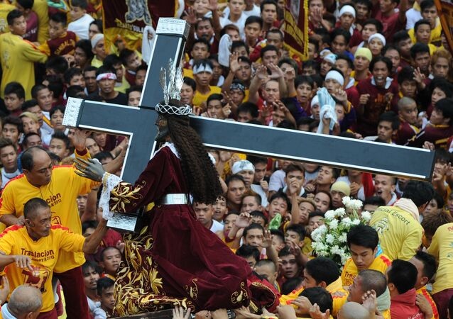 Catholic devotees carry the life-size statue of the Black Nazarene (C) to a carriage during an annual procession in honor of the centuries-old icon of Jesus Christ in Manila on January 9, 2013.