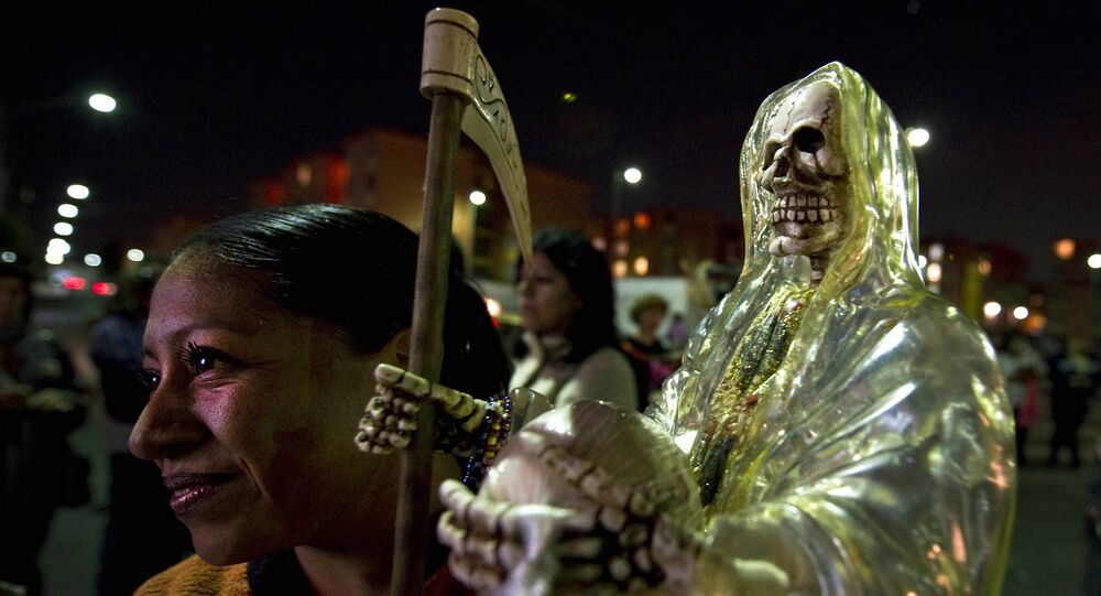 A devotee of the 'Santa Muerte' (Holy Death) holds a image as she prays at the shrine of the goddess at the Iztapalapa shantytown in Mexico City, on February 4, 2011.