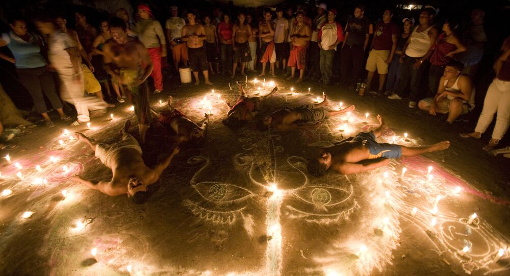 In this photo taken late Sunday, Oct. 11, 2009, followers of Maria Lionza's cult lie down inside a circle formed by candles during their annual ritual at Sorte Mountain, in Venezuela's Yaracuy state.
