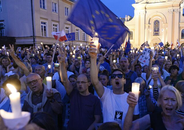 Anti-government protesters raise candles and shout slogans, as they gather in front of the Supreme Court in Warsaw, Poland, Saturday, July 22, 2017