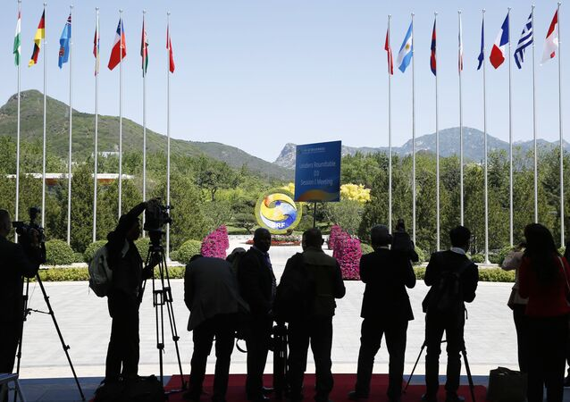 Journalist take pictures outside the venue of a summit at the Belt and Road Forum in Beijing, Monday, May 15, 2017