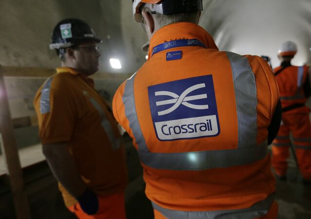 Workers talk as tunnel boring machine Victoria breaks into the eastern end of the Liverpool Street Crossrail station in London, Tuesday, March 10, 2015.