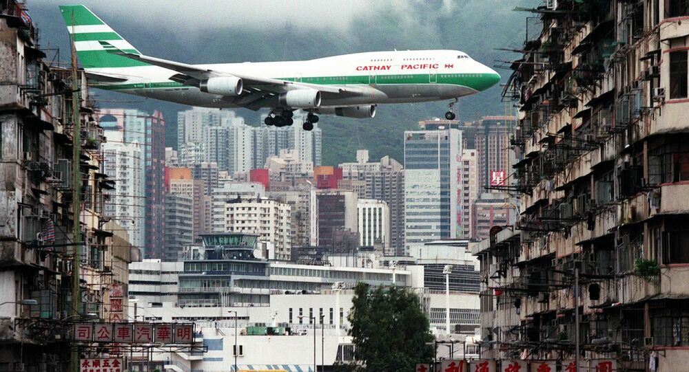 Hong Kong flag carrier Cathay Pacific, Boeing 747-400 jumbo jet, flies over the Kai Tak Airport control tower