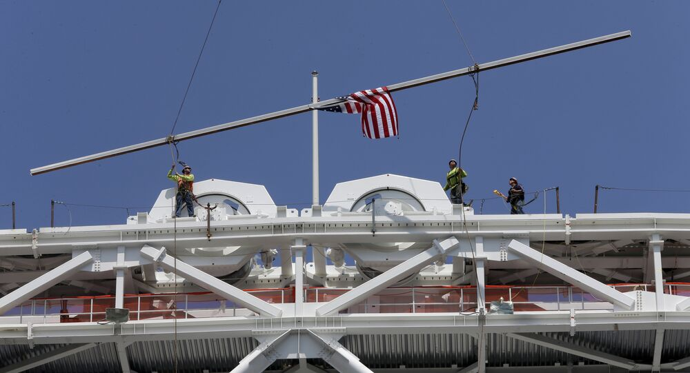 Construction workers place the final piece of steel in the superstructure that will support the retractable roof over the Arthur Ashe Stadium, Wednesday, June 10, 2015, in New York.