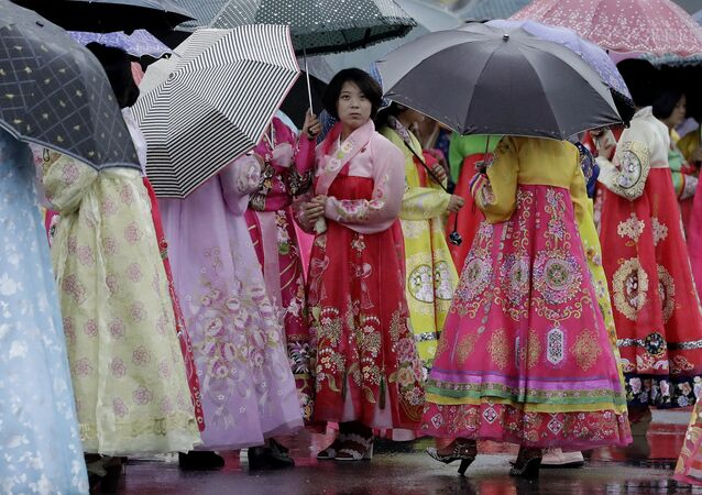 University students wearing traditional Korean dresses wait in the rain for the start of a mass dance on Thursday, July 27, 2017, in Pyongyang, North Korea as part of celebrations for the 64th anniversary of the armistice that ended the Korean War.