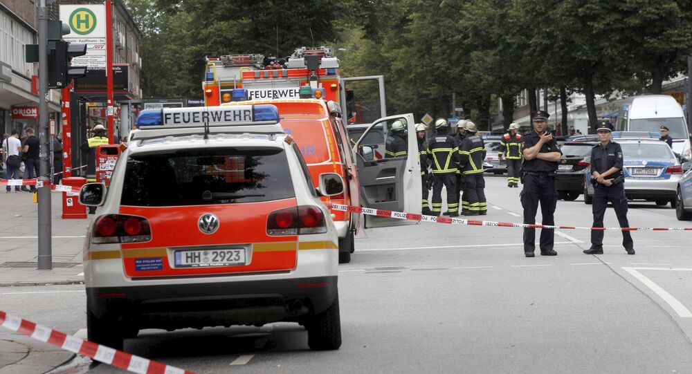 Police officers and fire engines stand in front of the supermarket in Hamburg, Germany, Friday, July 28