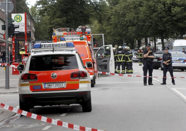 Police officers and fire engines stand in front of the supermarket in Hamburg, Germany, Friday, July 28, 2017, where a man with a knife fatally stabbed one person and wounded four others as he fled, police said