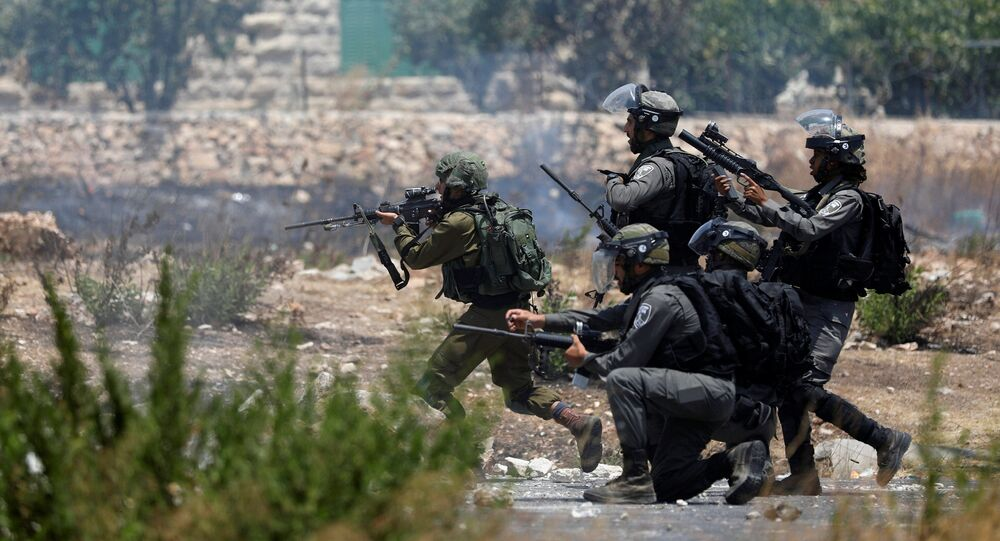 Israeli forces aim their weapons during clashes with Palestinian protesters near the Jewish settlement of Beit El, near the West Bank city of Ramallah July 24, 2017