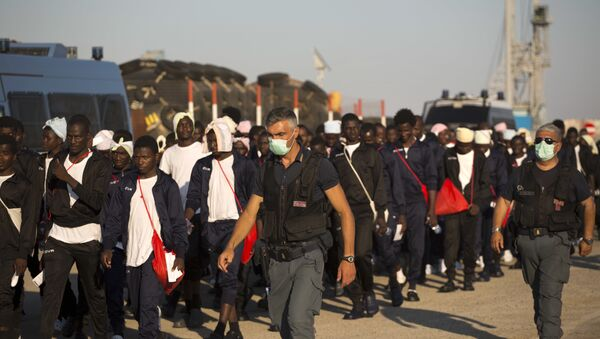 Italian border police officers escort sub Saharan men on their way to a relocation center, after arriving in the Golfo Azzurro rescue vessel at the port of Augusta, in Sicily, Italy, with hundreds of migrants aboard, rescued by members of Proactive Open Arms NGO, on Friday, June 23, 2017 - Sputnik International