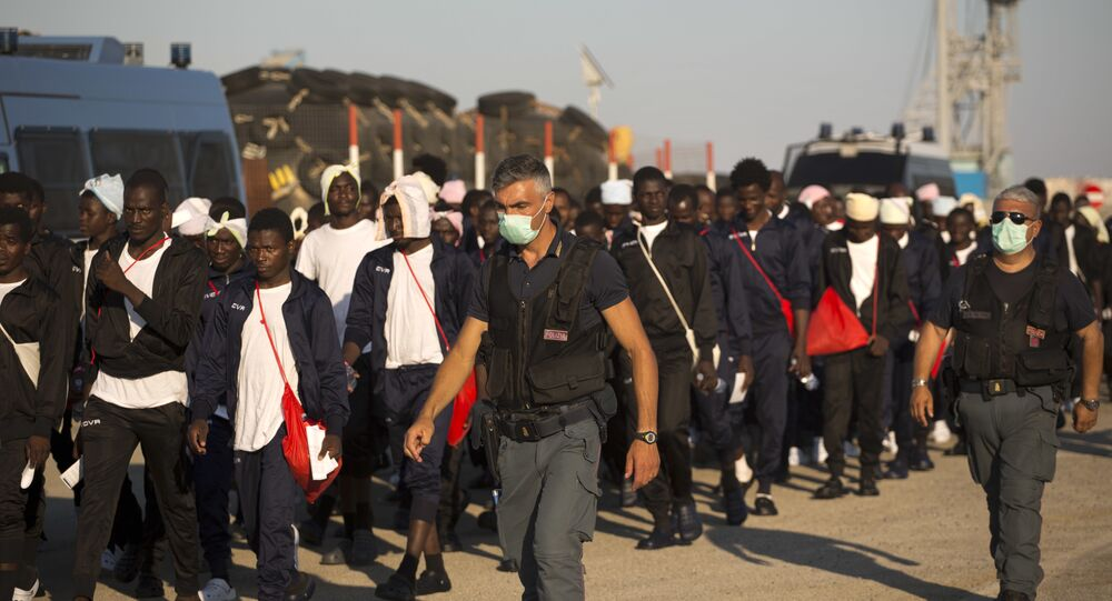 Italian border police officers escort sub Saharan men on their way to a relocation center, after arriving in the Golfo Azzurro rescue vessel at the port of Augusta, in Sicily, Italy, with hundreds of migrants aboard, rescued by members of Proactive Open Arms NGO, on Friday, June 23, 2017