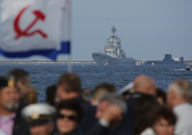 People gather to watch the Navy Day parade, with the Russian nuclear missile cruiser Pyotr Veliky (Peter the Great) and nuclear submarine Dmitry Donskoy seen in the background, in Kronshtadt, a seaport town in the suburb of St. Petersburg, Russia, July 30, 2017