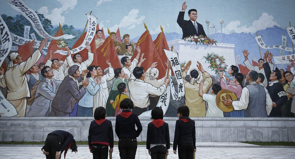 North Korean school girls holding brooms bow to pay their respects toward a mural which shows the late North Korean leader Kim Il-sung delivering a speech, before sweeping the area surrounding this mural on Tuesday, Dec. 1, 2015, in Pyongyang, North Korea