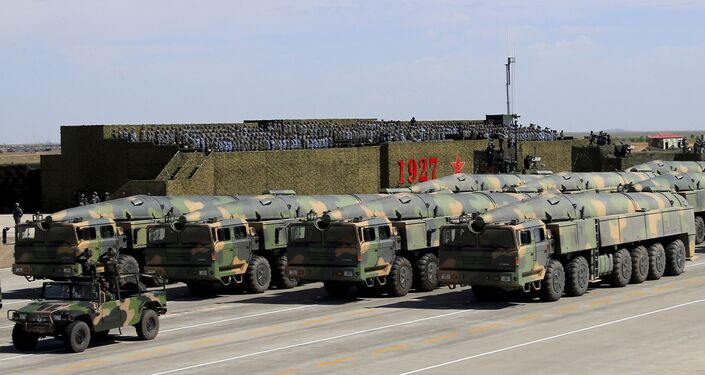 In this photo released by China's Xinhua News Agency, military vehicles carrying missiles for both nuclear and conventional strikes are driven past the VIP stage during a military parade to commemorate the 90th anniversary of the founding of the People's Liberation Army at Zhurihe training base in north China's Inner Mongolia Autonomous Region, Sunday, July 30, 2017