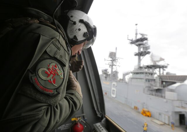 A crewman aboard a US Marine MV-22B Osprey aircraft looks out as it lifts off the deck of the USS Bonhomme Richard amphibious assault ship off the coast of Sydney, Australia, Thursday, 29 June 2017 after a ceremony on board the ship marking the start of Talisman Saber 2017, a biennial joint military exercise between the United States and Australia