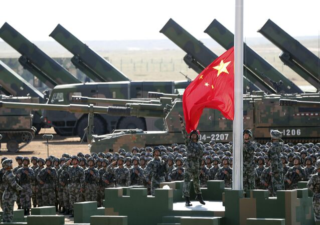 In this photo released by China's Xinhua News Agency, Chinese People's Liberation Army troops perform a flag raising ceremony, July 30, 2017 for a military parade to commemorate the 90th anniversary of the founding of the PLA on Aug. 1 at Zhurihe training base in north China's Inner Mongolia Autonomous Region