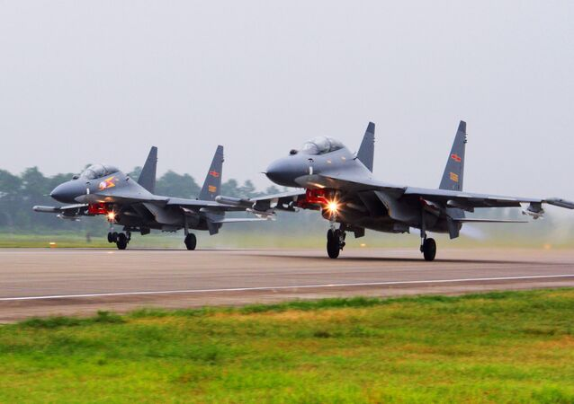 In this undated file photo released Saturday, Aug. 6, 2016, by China's Xinhua News Agency, two Chinese SU-30 fighter jets take off from an unspecified location to fly a patrol over the South China Sea