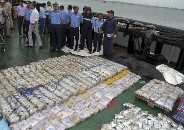 In this Sunday, July 30, 2017 photo, Indian coast guard officials, in blue, stand next to a massive amount of heroin they claim to have seized from a ship off the country's western coast near Porbandar, India