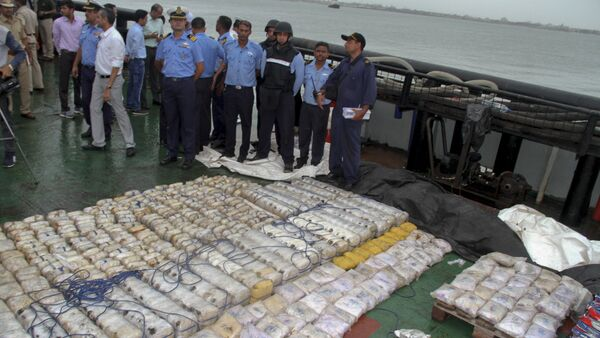 In this Sunday, July 30, 2017 photo, Indian coast guard officials, in blue, stand next to a massive amount of heroin they claim to have seized from a ship off the country's western coast near Porbandar, India - Sputnik International