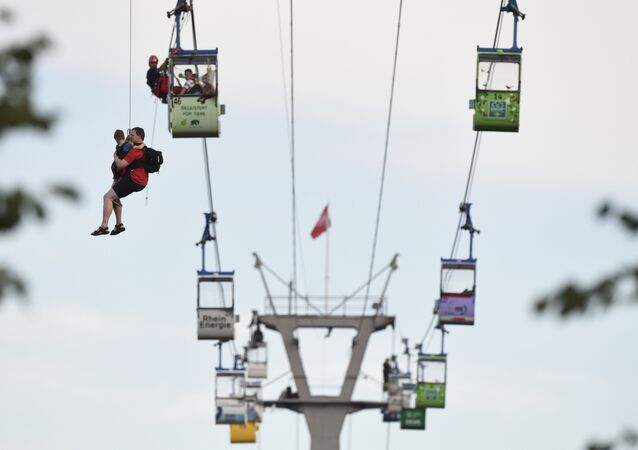 Members of the fire service rescue people from cable car gondolas, in Cologne, Germany, Sunday, July 30, 2017.