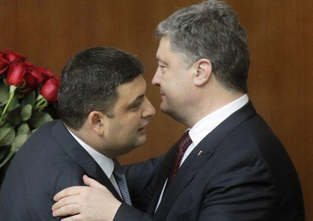 Ukraine's President Petro Poroshenko, right, and Prime Minister Volodymyr Groysman celebrate after Groysman was appointed the Prime Minister during the Ukrainian parliament session in Kiev, Ukraine, Thursday, April 14, 2016