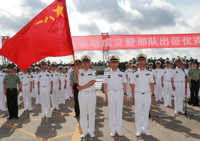 A soldier of China's People's Liberation Army (PLA) is holding a PLA flag as others stand guard at a military port in Zhanjiang, Guangdong province, China, July 11, 2017