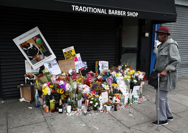 A woman looks at floral tributes laid after the death of Rashan Charles outside a shop in east London