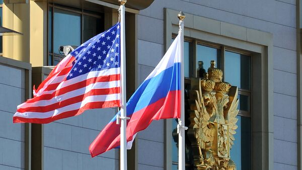 This photo taken on May 7, 2013 shows Russian and the US flags running up as the US Secretary of State arrives at Moscow Vnukovo Airport - Sputnik International