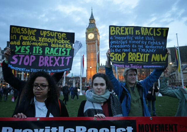 Protesters hold up anti-Brexit placards as they take part in a protest in support of an amendment to guarantee legal status of EU citizens, outside the Houses of Parliament in London on March 13, 2017
