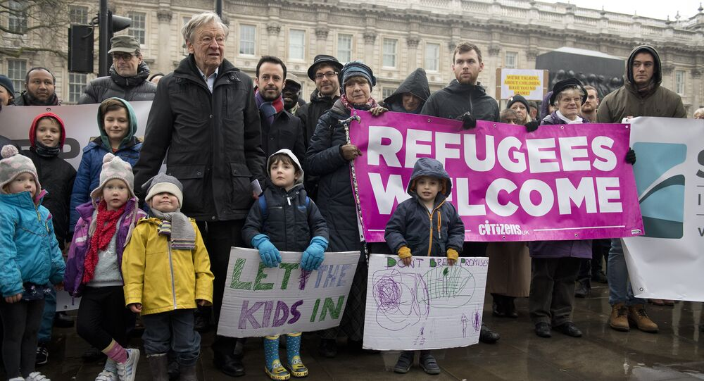 People gather to hear speeches on Whitehall before Lord Alf Dubs (6L) handed in a petition to 10 Downing Street calling on the Prime Minister to reconsider the decision to close the 'Dubs' scheme to take refugee children into the UK in London on February 11, 2017