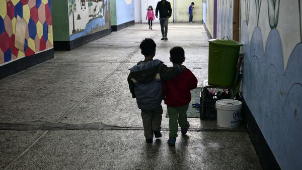 Children walk through a former industrial warehouse at the Oinofyta refugee camp, some 60 km north of Athens, on 13 March 2017 in Oinofyta - Sputnik International