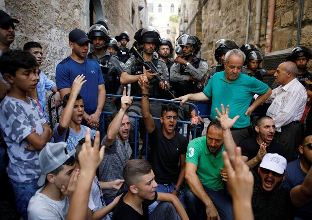 Palestinians shout slogans as Israeli border police officers guard in Jerusalem's Old City July 27, 2017