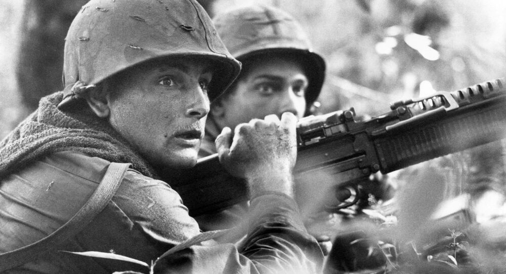 U.S. machine gunner Spc. 4 James R. Pointer, left, of Cedartown, Ga., and Pfc. Herald Spracklen of Effingham, Ill., peer from the brush of an overgrown rubber plantation near the Special Forces camp at Bu Dop during a half hour firefight, Dec. 5, 1967