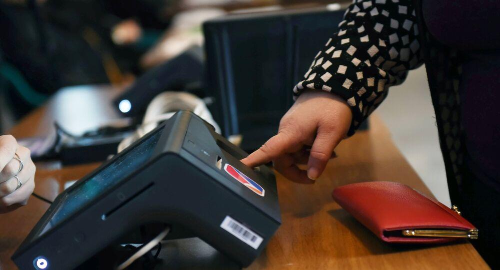 A woman touches a fingerprint scanner